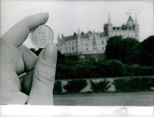 A hand holding a coin and being compared to the castle at the hill.