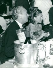 Man and woman in a formal attire, eating and having a conversation with someone, August 1967.