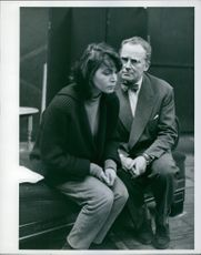Actress Eva Bartok is sitting with a man with upset face .