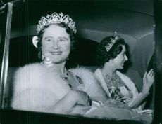 Elizabeth Angela Marguerite Bowes-Lyon with her daughter Princess Margaret inside the car and smiling at people.