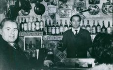 """People standing in a bar, with a bartender making drinks.  """"__ movement Rex""""  1970"""