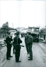 A vintage photo of two Army official together with a civilian people having a conversation along the street in March 18, 1964.