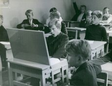 Childhood photo of Carl XVI Gustaf, in a classroom.