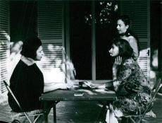 Women playing cards and smiling.