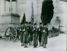 Guards standing, looking towards the camera while holding flags in hands.