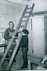Man and child placing ladder.