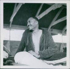 Robert Wells siting while smiling in Korea, 1950.