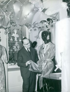 Augustin Dabadie looking at the clothes that's worn by a mannequin.