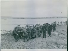 Soldiers pulling a tank  and others pushing the back to move it from a rocky path by the water during Finnish war, 1944.