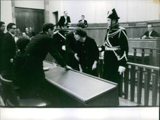 Policemen holding a woman in the courtroom.