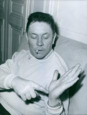 """Man showing the palm of his hand while smoking.   """"Henri __""""  1964"""