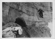 German soldier climbing, trying to take a look into the cave in Caucasus.