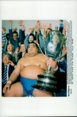 Japanese sumo champion Musashimaru shows up his Emperor's Cup after the win against Yokozuna.