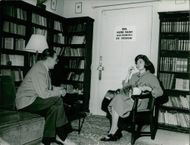 Soraya with a cat on her lap, talking to a man.