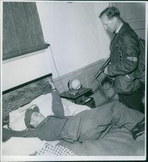 A soldier standing pointing gun at another soldier lying on bed and smiling.