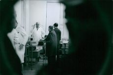 """A photo of men talking to each other in laboratory.  """"Professor __ """"  1968"""
