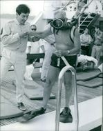 French socialist politician Gaston Defferre is taking step to diving, a men assisting him