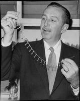 Walt Disney shows off his miniatures he made of all his twenty Oscars.