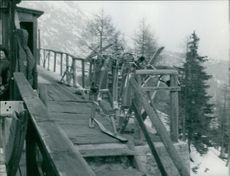 Snow bikes piled up in the corner.  - Mar 1963