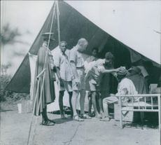 Group of soldiers giving medication to the patients.