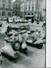 A photo of motorcycles parked on the side of the street. 1961