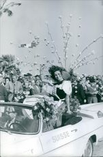 People cheers for Miss Schweiz, Yvette Revelly as she waves and smiles to the crowd at the parade.