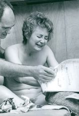 Woman sharing a laugh with a man while looking at the newspaper.