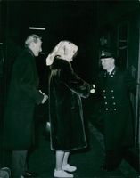 Guard shaking hands with a woman and smiling, another man standing beside looking at them.