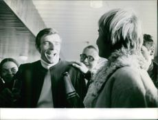 Jean-Claude Killy smiling while being surrounded by people.