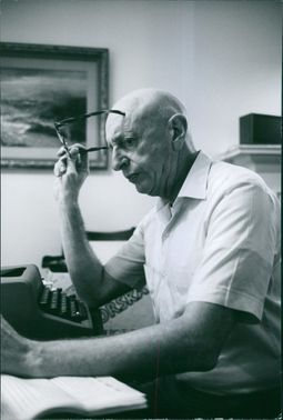 An old man holding his glasses, while sitting in front of a typewriter.