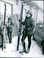 Skiers standing and holding skis.