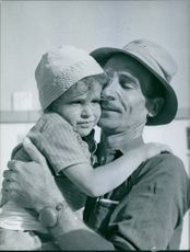 1968  A photo of a man holding a baby and smiling.