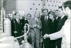 Royal couple Juan Carlos and Queen Sofía standing with people and looking at machine.