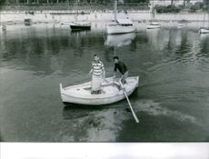 Man and woman in boat, man rowing.