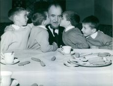 1967  A scene of children kissing their father when taking breakfast.