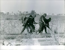 Soldiers helping to transport a wounded soldier in Bizerte during the Bizerte Crisis. Photo taken on July 26, 1961.