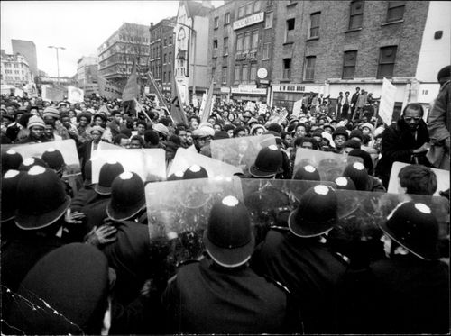 A wall of policemen holds back the marchers