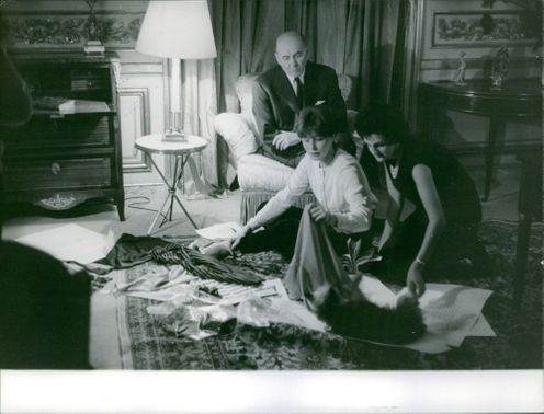 Bettina packing clothes with a woman, man looking at them.
