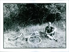 A man sitting on the grass beside a bicycle.