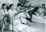 Two men (one pipe smoking) and two women, all of them writing on pads.