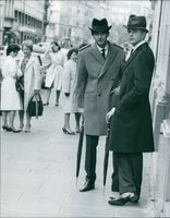 Women swoon over Bob Asklof, as he stands on the sidewalk with another man, 1963.