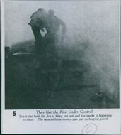 A photo of two soldier trying to put out the fire in the tank during second world war.