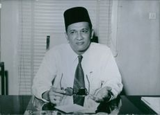 Inche Abdul Hamid Bin Haji Jumat sittig behind the desk  and holding sunglasses.
