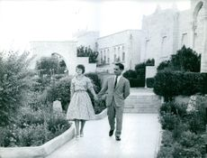 King Hussein of Jordan I and Princess Muna al-Hussein holding hands while walking along the pathway.