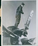 A Ninth US Air Force crewman brushing the snow on the plane's propeller.