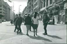 Civilians and soldiers crossing the street.