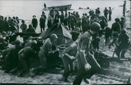 Soldiers pushing something at the beach.