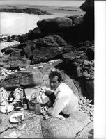 Bernard Buffet having picnic on rocks.