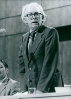 Michael Foot is a British Politician, serving as Lord President of the Council and Leader of the House of Commons; standing in a conference.