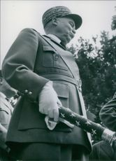 A photograph of a military, holding command baton in his hand.